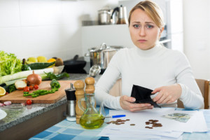 smutna kobieta pokazuje pusty portfel