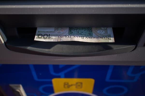 100 złotych wychodzące ze szczeliny bankomatu