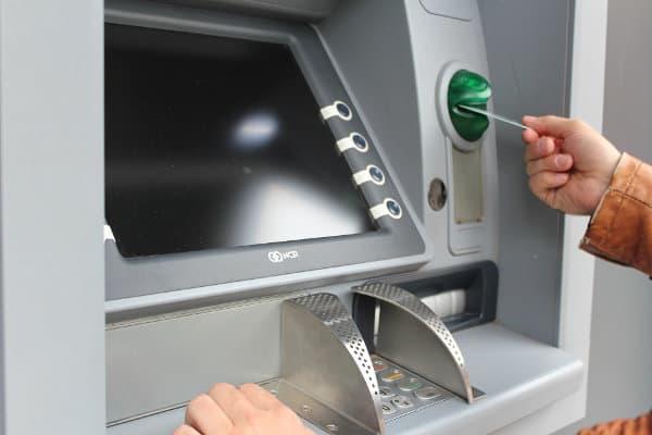 Mężczyzna wkłada kartę do bankomatu
