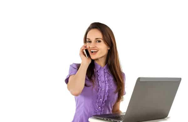 Kobieta rozmawia przez telefon komórkowy siedząc przy laptopie