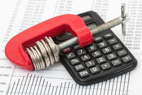 Kalkulator i monety ściśnięte w imadle