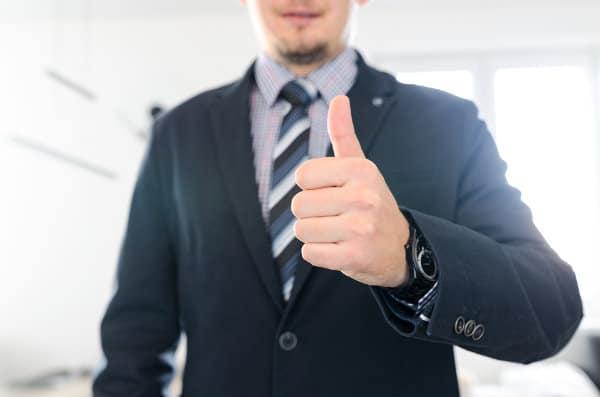 Mężczyzna w garniturze wskazuje kciuk do góry