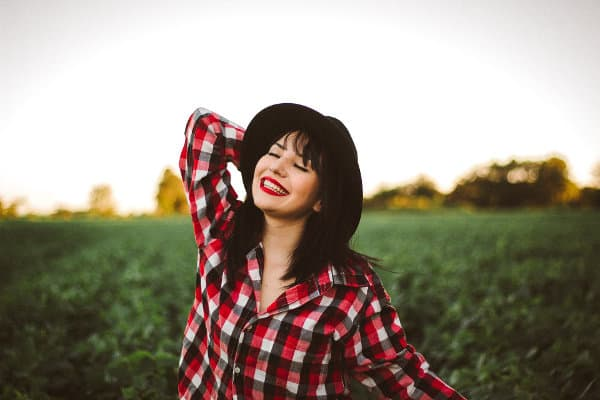 Kobieta we flanelowej koszuli i kapeluszu uśmiecha się