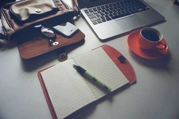 Laptop leży koło kubka kawy i notesu