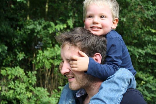 Ojciec trzyma swojego małego synka na barana