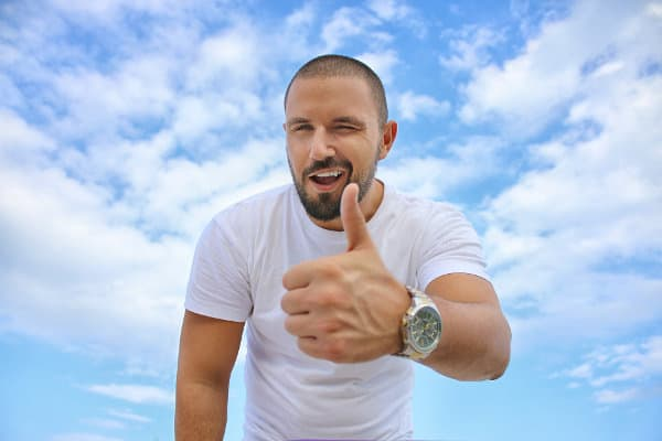 Mężczyzna pokazuje wyciągnięty w górę kciuk