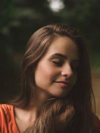 Kobieta z zamkniętymi oczami delikatnie się uśmiecha