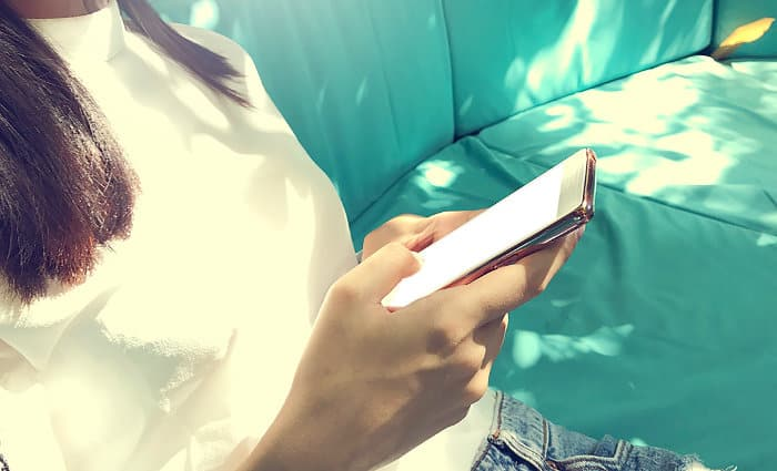 Kobieta siedzi na kanapie i sprawdza telefon komórkowy