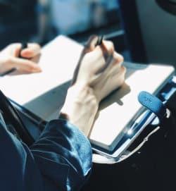 Kobieta trzyma w dłoni notatnik