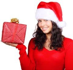 Kobieta w czapce Mikołaja trzyma prezent